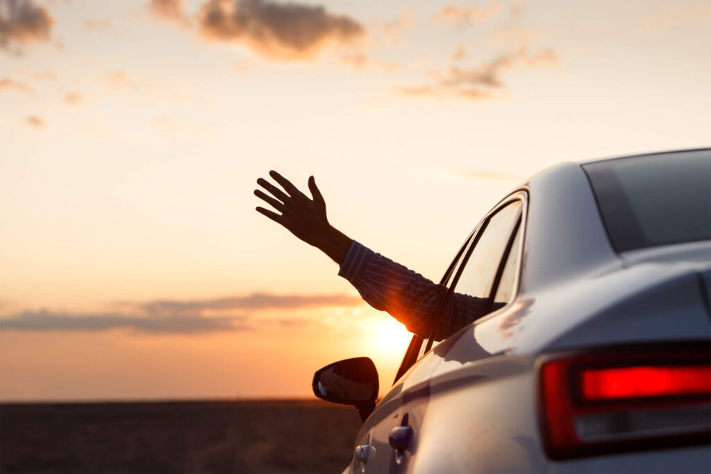 man-inside-car-showing-his-hand-outdoor-leaning-out-car-window-sunset