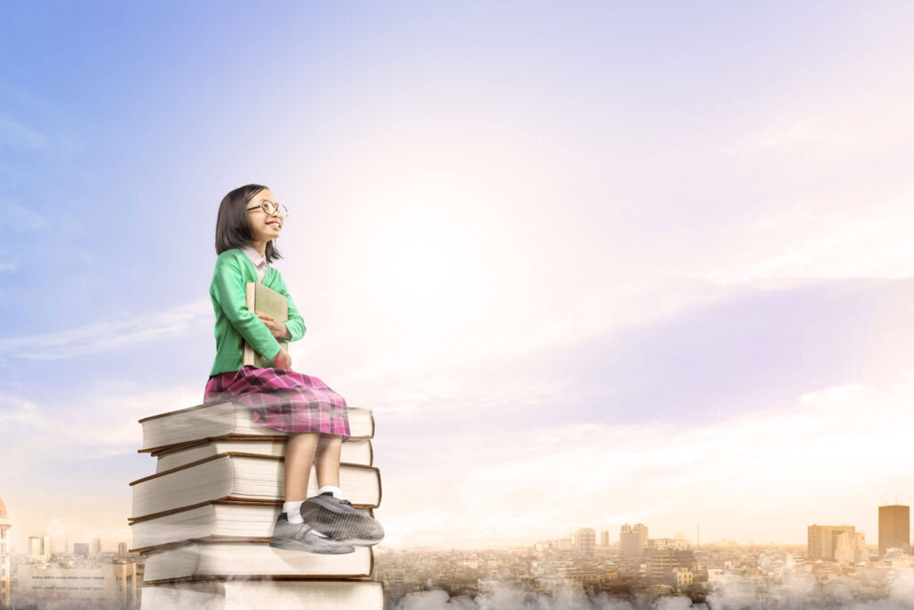 asian-cute-girl-with-glasses-holding-book-while-sitting-pile-books-with-city-blue-sky